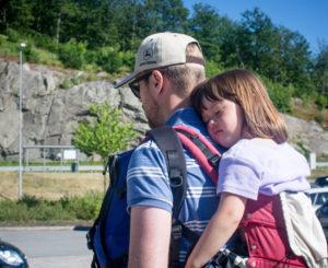 Far som bærer fireåring på ryggen i bæresele