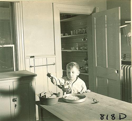 Boy using hand food grinder, The University of Iowa, January 12, 1938